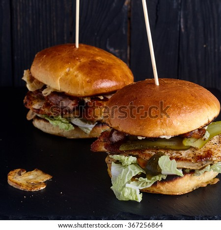 Two chicken burgers with mushroom and cheese sauce on dark wood background - stock photo