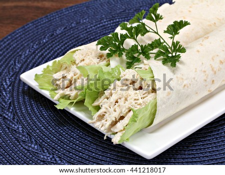 Two chicken caesar wraps with shredded chicken, lettuce and parmesan cheese garnished with parsley.  Close up, partial view.