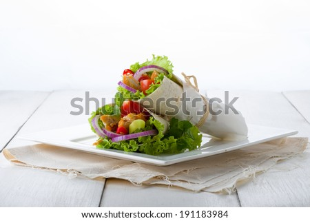 Two chicken tortillas or tacos with a healthy salad filling served wrapped in paper on a plate for a tasty Tex-Mex meal - stock photo