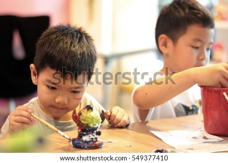 Two Child painting a ceramic pottery model.