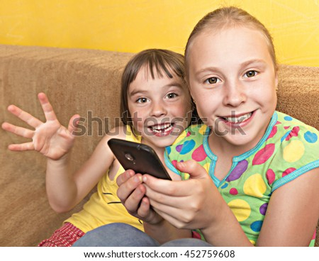Two child play on your mobile phone. - stock photo