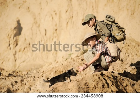 Two children, a boy and a girl archaeologists come with equipment to dig a little puppy with a summer hot day - stock photo