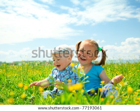 Two children (a girl and a boy) are having fun on green meadow - stock photo