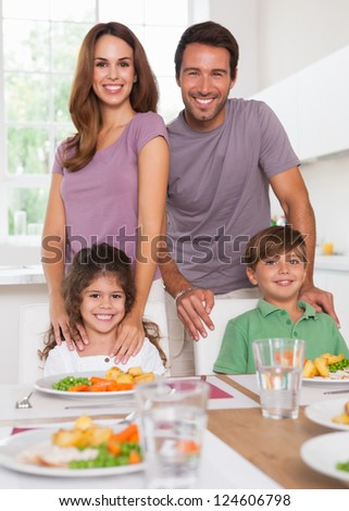 Two children and their parents smiling at the camera at dinner table in kitchen - stock photo