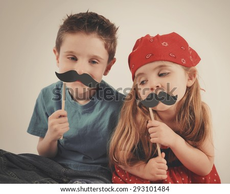 Two children are playing dress up with fake mustaches on an isolated background for a creative or imagination concept. - stock photo