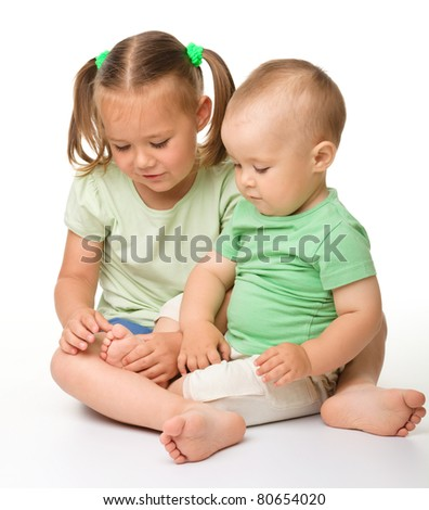 Two children are playing while sitting on the floor, isolated over white - stock photo
