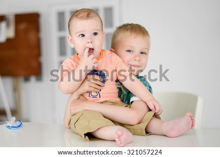 Two children are playing while sitting together at home . - stock photo