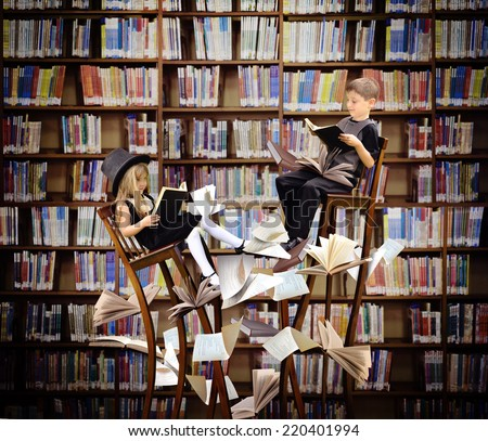 Two children are reading books on long, surreal wooden chairs in a library with books and papers flying around them for an education or imagination concept. - stock photo