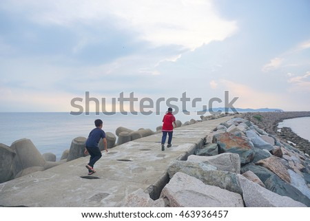 Two children are running along the rocky beach