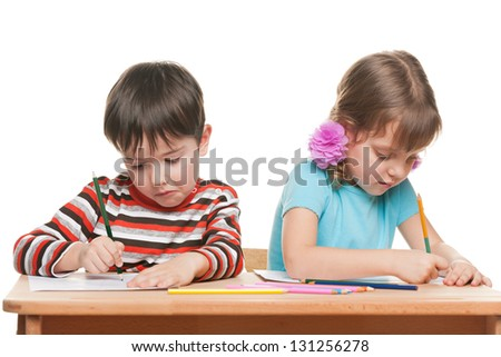 Two children are sitting at the desk and write