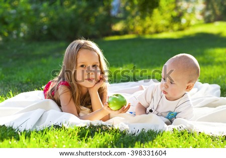 Two children baby brother and sister on green meadow. Summer park - stock photo
