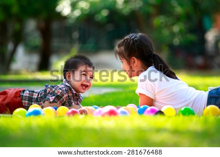 Two children, big syster and her young brother are laying on green - stock photo