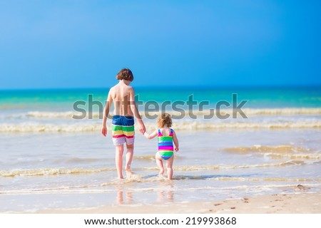 Two children, boy and girl in colorful swimming suit, walking on a beautiful tropical beach holding hands, view from the back - stock photo