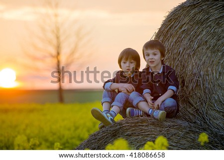 Two children, boy brothers in a oilseed rape field, sitting on a bale of haystacks, watching the sunset