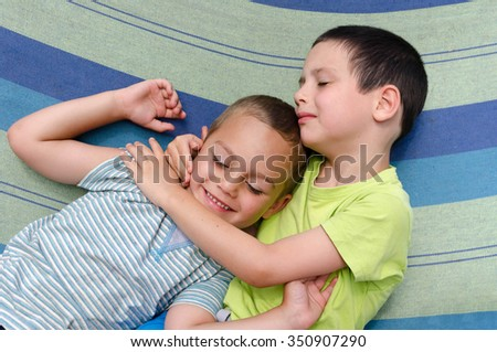 Two children boys hugging and resting or sleeping in hammock in summer - stock photo