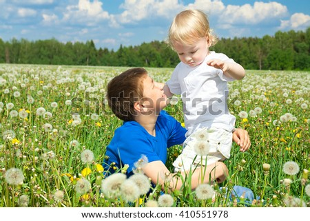two children boys play on a summer meadow - stock photo