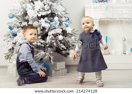 Two children (brother and sister) near christmas tree. Boy sitting under tree. Girl walking out of frame. - stock photo