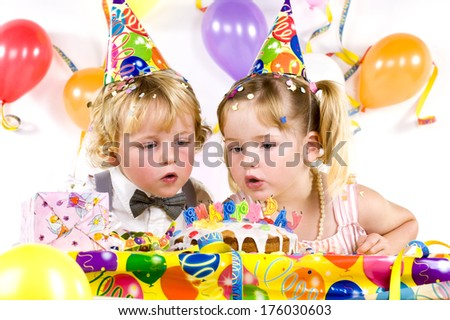 Two children celebrating a birthday with a cake.