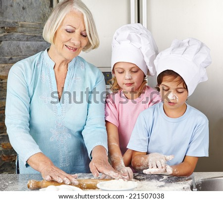 Two children cooking together with grandmother for christmas in a kitchen - stock photo