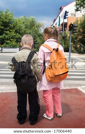 two children crossing the street - stock photo