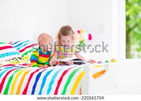 Two children, curly little toddler girl and funny baby boy, brother and sister, reading a book sitting in sunny bedroom on wooden white bed with colorful rainbow bedding enjoying nice weekend morning - stock photo