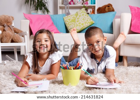 Two children drawing in the living room - stock photo