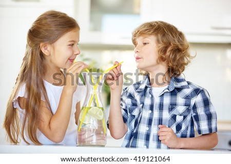 Two children drinking fresh water with straw in the kitchen - stock photo