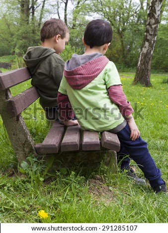 Two children friends or brothers on a bench in spring park, back view.