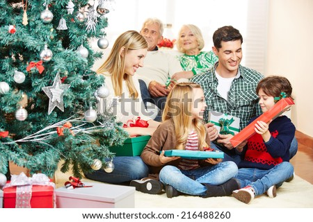 Two children getting gifts at christmas eve from parents and grandparents - stock photo