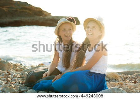 Two children girls with hats sitting on the beach and smiling
