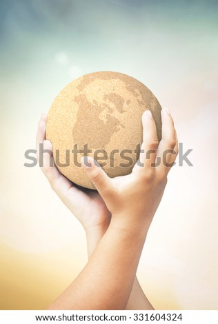 Two children hands holding paper world ball. Paper in human hand over blurred nature background. E-learning Education, Internet Library, World Environment Day concept. - stock photo