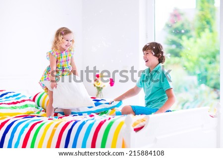 Two children, happy laughing boy and cute curly little girl having fun at pillow fight with feathers in the air jumping, laughing and giggling in a white bedroom with colorful bedding - stock photo