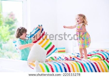 Two children, happy laughing boy and cute curly little girl having fun at pillow fight with feathers in the air jumping, laughing in a white bedroom with colorful bedding. Focus on jumping girl. - stock photo