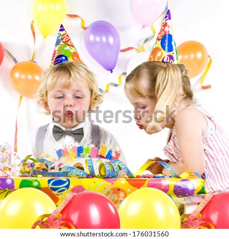 Two children having a party blowing out candles on a cake.