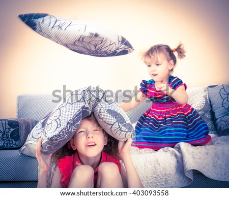 Two children having fun at pillow fight with feathers in the air jumping, laughing and giggling  - stock photo