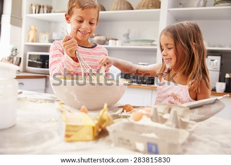 Two children having fun baking in the kitchen - stock photo