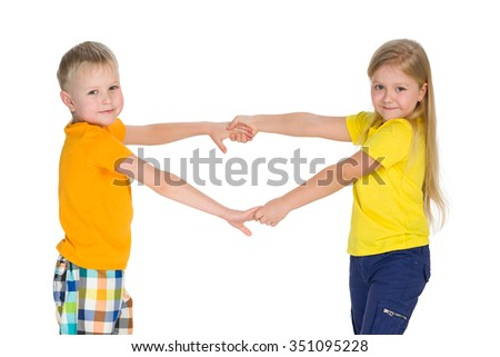 Two children hold hands against the white background - stock photo