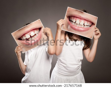 two children holding a picture of a mouth smiling - stock photo