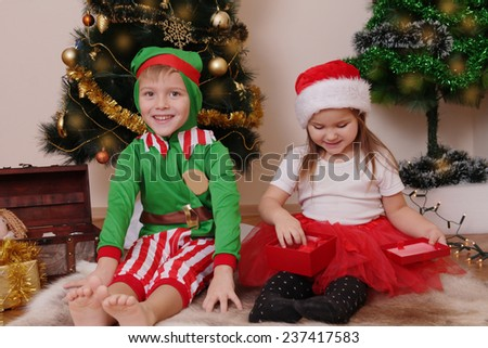 Two children in Christmas costumes opening presents
