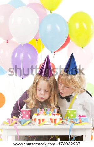 Two children in party hats blowing out birthday candles.