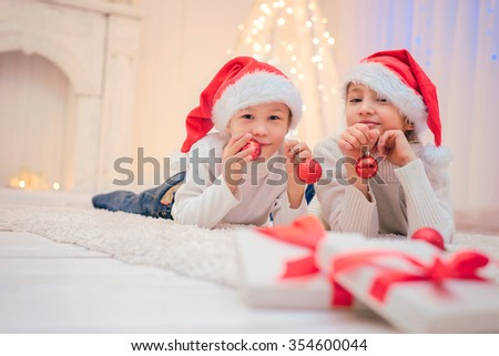Two children in Santa hat with Christmas decorations . - stock photo
