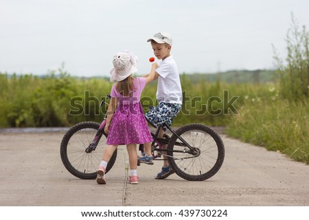 Two children in summer day bicycle and flower boy and girl - stock photo