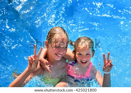 Two children in swimming pool . Children hugging and gesticulate hand victory sign.  Summer holiday.  Outdoor. Girl holding her sister in her arms. Children  activities lifestyle. - stock photo