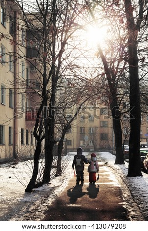Two children in the city going from school in a Sunny winter day