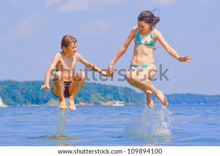 Two children jumping in water - stock photo