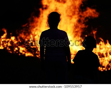 Two children looking at big fire