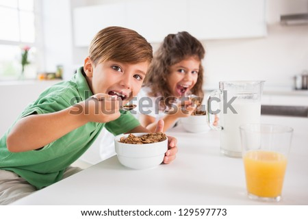Two children looking at camera while eating cereal in kitchen