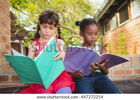 Two children looking their book at school