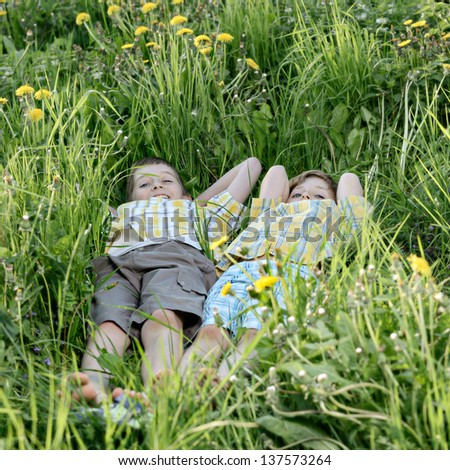 two children lying on the grass in spring park. - stock photo