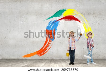 Two children of school age painting wall in colors - stock photo
